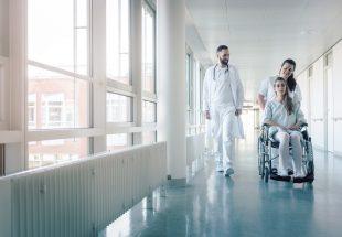 Médecin, infirmière et une patiente en fauteuil roulant dans les couloirs d'un hôpital
