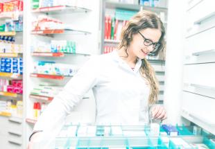 Pharmacienne cherchant un médicament dans un meuble à tiroirs