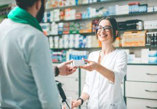 Pharmacienne souriante donnant un médicament à un client