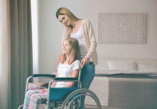 Une femme aide une adolescente en fauteuil roulant, toutes deux souriantes