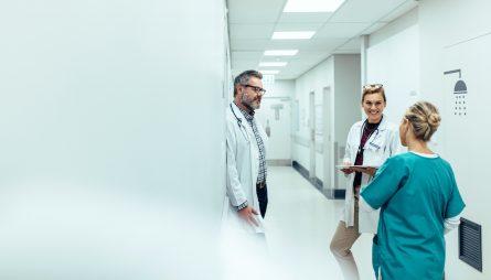 Equipe médicale qui discute dans les couloirs d'un hôpital