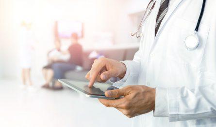Un médecin avec un stéthoscope utilise une tablette pour vérifier l'état de ses patients