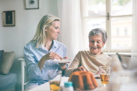 Une dame âgée en fauteuil reçoit de la visite pour le goûter