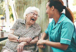 Une dame âgée rit aux éclats auprès d'une infirmière
